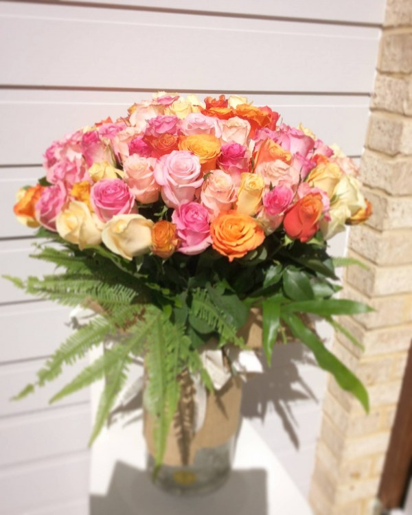 a large cylinder vase filled with 100 roses in pink and peach.