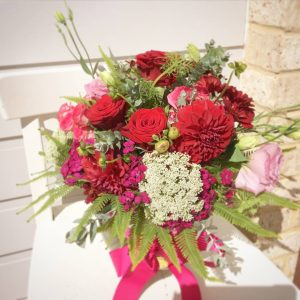 a glass fishbowl arrangement of red dahlias, red roses, queen annes lace and pink lissianthus.