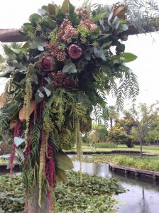 a wooden arbour covered with native flowers and foliages.