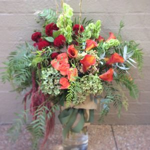 a clear glass vase filled with orange and red seasonal flowers with lime green accents.