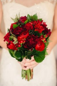 a close up image of a bride holding a bouquet of deep red and burgundy flowers.