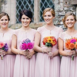 4 bridesmaids in soft pink dresses, standing outside a church holding brightly coloured bouquets, each one individual.