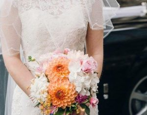 a veiled bride holding her bouquet of peach, pink and white flowers.