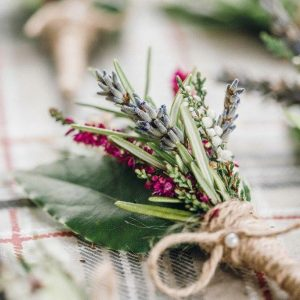 a close up grainy image of a natural buttonhole of herbs and heather.