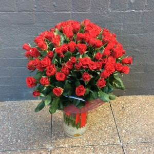 a large cylinder vase filled with 100 long stem red roses.
