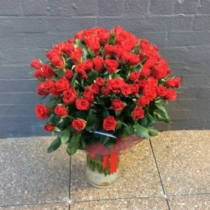 a large cylinder vase filled with 100 long stem red roses.