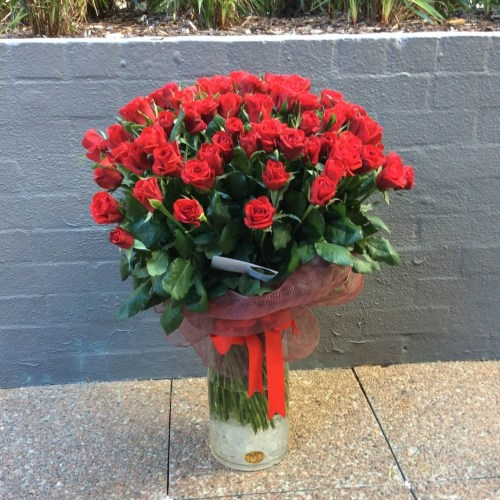 a large cylinder vase filled with 100 long stem red roses