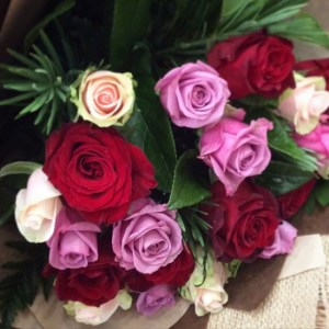 a close up image of a posy style bouquet of 12 coloured roses.