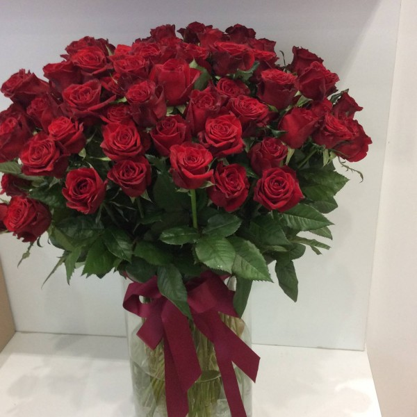 100 red roses in cylinder vase with burgundy bow