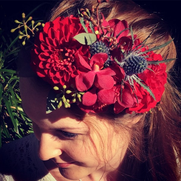 a floral headpiece made using red dahlias and orchids