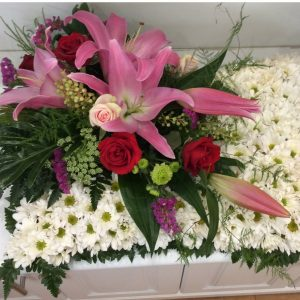 a sympathy pillow tribute of white dasies with a pink oriental lily and red rose feature on the left