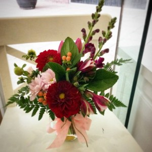 a jar filled with red and pink flowers.- A Touch of Class Florist