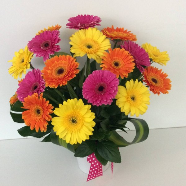 a brightly coloured arrangement of gerberas in pink, yellow and orange