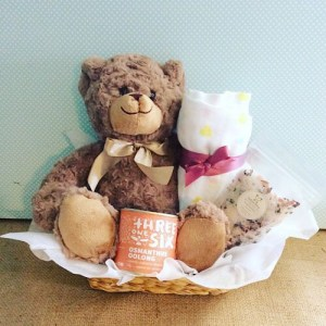 Mummy and Me Hamper in Pink - contains a soft teddy, a muslin wrap, a threeonesix tea, and salted bliss bath salt sachet all packaged in a seagrass basket - A Touch of Class florist