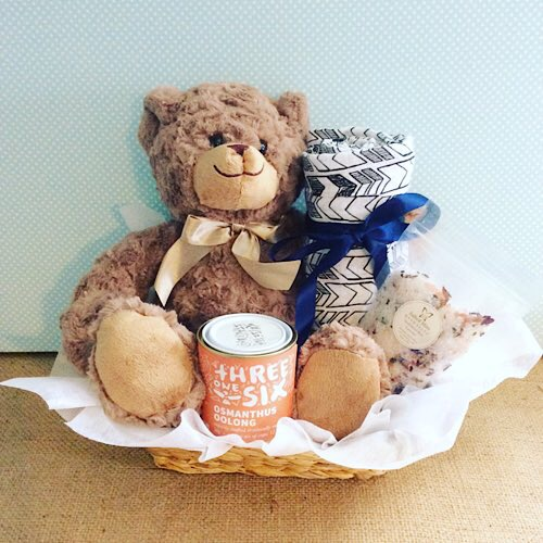 Mummy and Me Hamper in blue - contains a soft teddy bear, a muslin wrap, and Threeonesix Tea and a Salted Bliss Bath salts sachet all wrapped up in a seagrass basket - A Touch of Class Florist