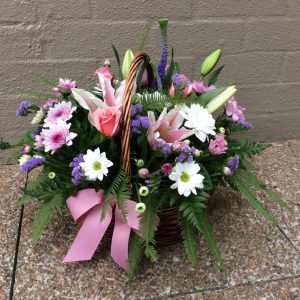 a wicker basket filled with seasonal flowers in feminine colours