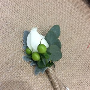 a simple lapel buttonhole with a white rose, green berries and eucalyptus leaves