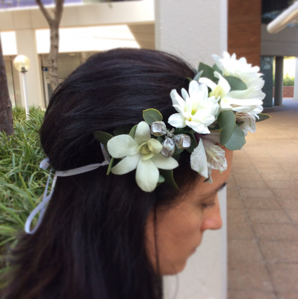 a half flower crown made using white flowers which ties at the back of your head with white ribbon.