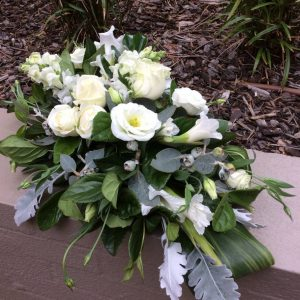 a full casket spray funeral tribute with white and green flowers