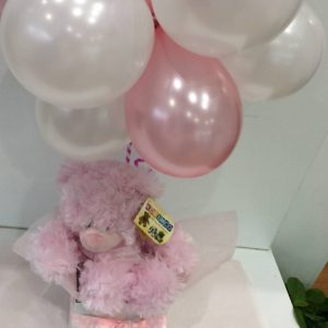 a cluster of 12 small balloons in pink and white with a pink fluffy teddy bear.