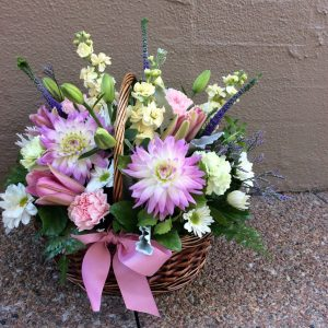 a wicker basket filled with seasonal flowers in pink, white, lemon and lilac