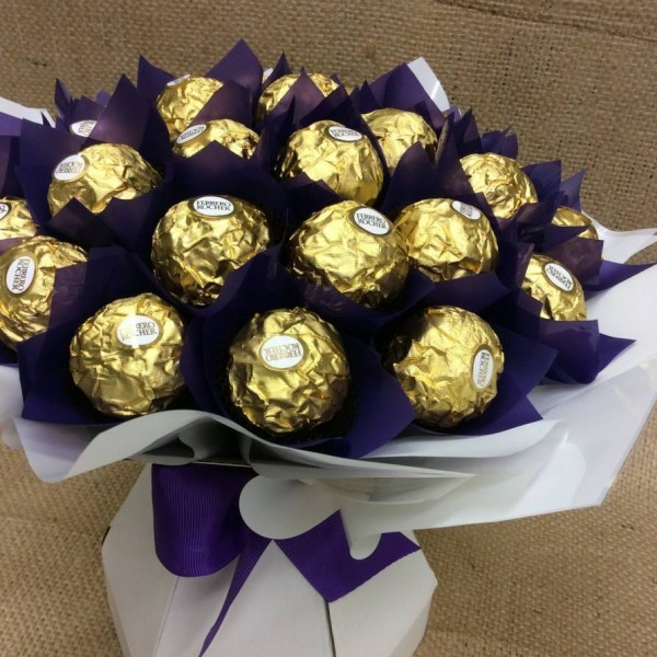 a posy style chocolate bouquet of ferrero rocher chocolates wrapped in dockers colours purple and white.