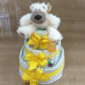 a 3 tiered nappy cake in neutral colours with yellow bows and a yellow bottle.
