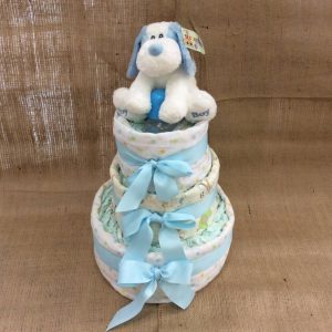 a 3 tiered nappy cake in blue with blue swaddle wraps, blue bows, a blue bottle and a blue puppy toy.