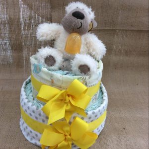 a 2 tiered nappy cake in unisex colours with yellow bows, grey swaddle wraps and a cream teddy.