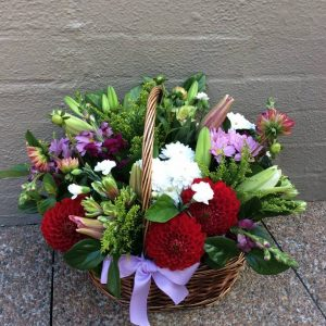 a wicker basket filled with cottage garden style flowers in pink, red, white and purple.