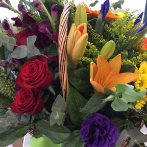 a wicker basket filled with seasonal flowers in bright colours