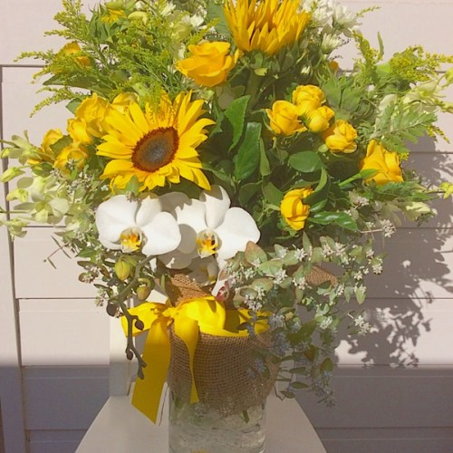 A large cylinder glass vase arrangement in bright sunshiny tones- A Touch of Class Florist