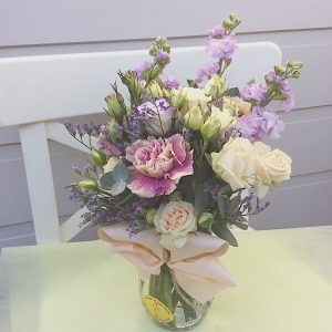 A cute jam jar of seasonal blooms in soft colours