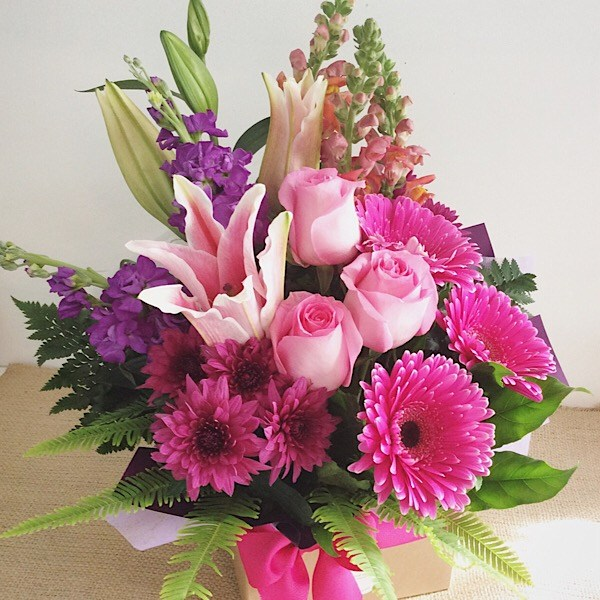 Hot Stuff Box Arrangement, in pink, purple and a touch of orange blooms.- A Touch of Class Florist