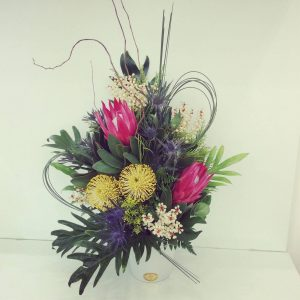 a striking, structural arrangement of native flowers and tropical leaves.