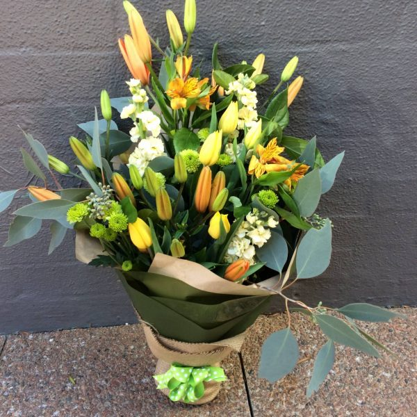 a bright yellow, green and gold bouquet with natural wrap and a green bow.