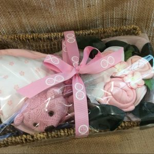 a seagrass basket filled with a knitted rattle toy in pink, a cluster of baby clothing flowers and a baby sleeping bag.