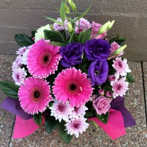 a pink and purple box arrangement featuring gerberas.