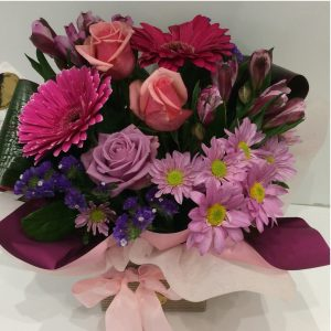 a vibrant box arrangement of pink and purple flowers featuring gerberas.