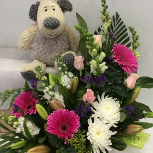 a floral arrangement in pink and purple with a teddy bear