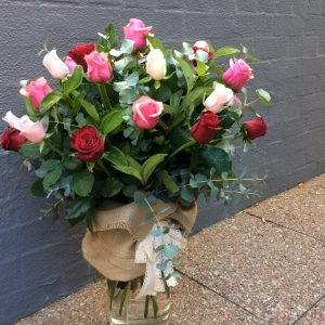 a large glass vase filled with coloured roses and wrapped in hessian with a lace bow.