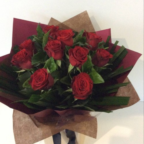 12 red roses in a compact posy style.