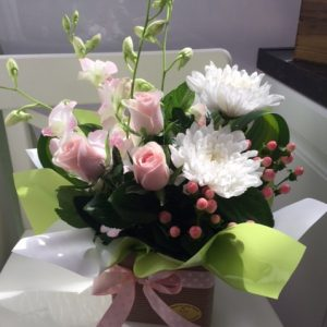 a posy box arrangement of seasonal flowers in pastel shades.