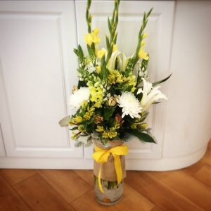 a large glass vase filled with yellow white and green flowers.
