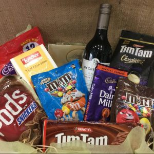 a hamper filled with chocolate products with a bottle of red wine