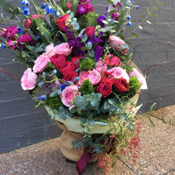 a large front facing hand tied bouquet in pink, purple and green.