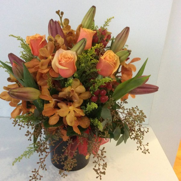 a tin pail arrangement of orange and gold flowers with textural foliage.