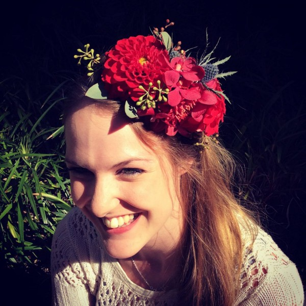 a girl wearing in her hair a green floral fascinator