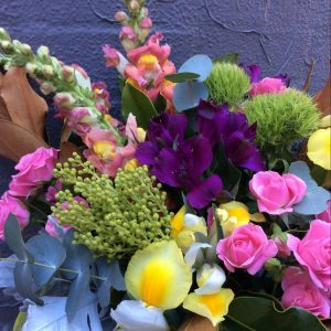 a bright bunch of seasonal flowers and foliage in pink, purple, yellow and green.