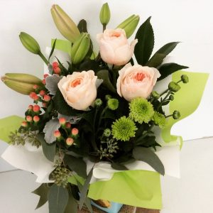 a simple box arrangement of seasonal flowers in pastel shades